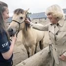 The Duchess of Cornwall meets River the pony and her handler Charlotte Hutchison (Jane Barlow/PA)