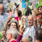 Environmental campaigners sound their mobile phone alarms together as they take part in the 'Time Is Now' mass lobby (Dominic Lipinski/PA)