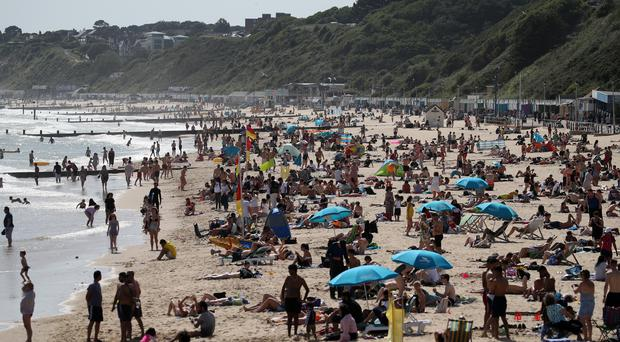 People enjoy the warm weather on Bournemouth beach in Dorset (Andrew Matthews/PA).