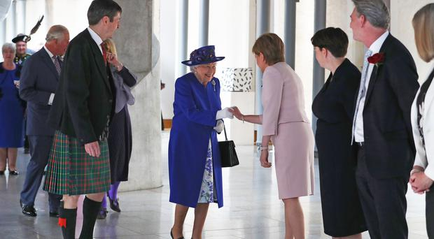 The Queen is greeted by First Minister Nicola Sturgeon as she arrives at the Scottish Parliament (Jane Barlow/PA)