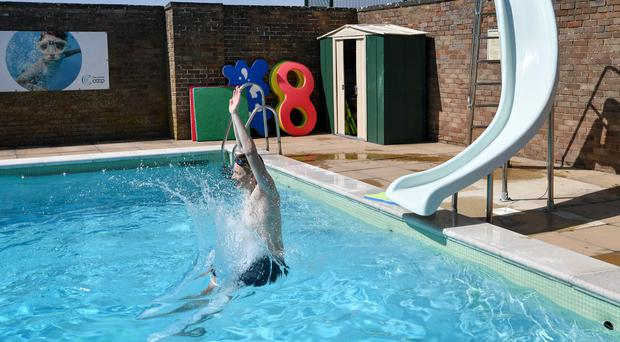 A swimmer uses the slide at the Lido in Chipping Norton in Oxfordshire (PA)