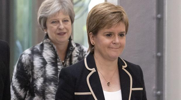 Nicola Sturgeon has said a review of devolution, to be announced by Theresa May, is a 'desperate act' (Jane Barlow/PA)