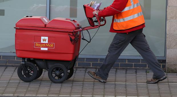 A postman delivers letters in Woking (PA)