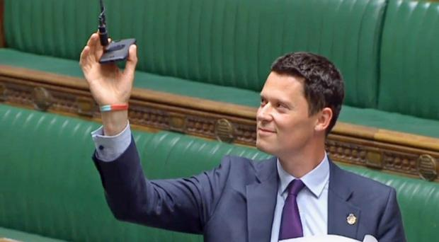 Tory MP Alex Chalk holds up his mobile phone to a microphone in the chamber of the House of Commons (House of Commons/PA)