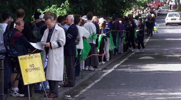Fans queue outside the ground for the start of the Wimbledon tennis Championships. (Toby Melville/PA)