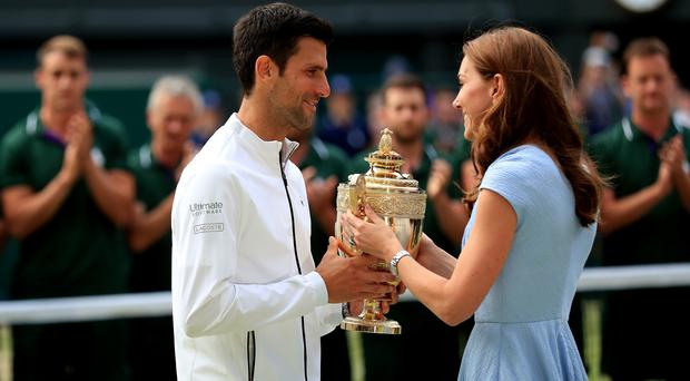 Novak Djokovic is presented the winner's trophy by the Duchess of Cambridge (Mike Egerton/PA)