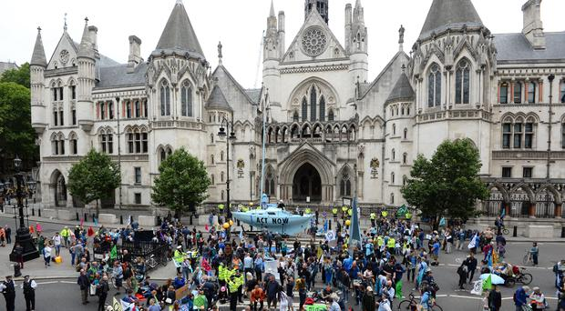 Protesters from Extinction Rebellion with a boat they have parked outside the Royal Courts of Justice in London (Kirsty O'Connor/PA)