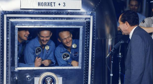 Armstrong, Collins, and Aldrin in their Isolation van on-board the recovery ship U.S.S Hornet being greeted by US President Richard Nixon (Nasa/Kipp Teague)