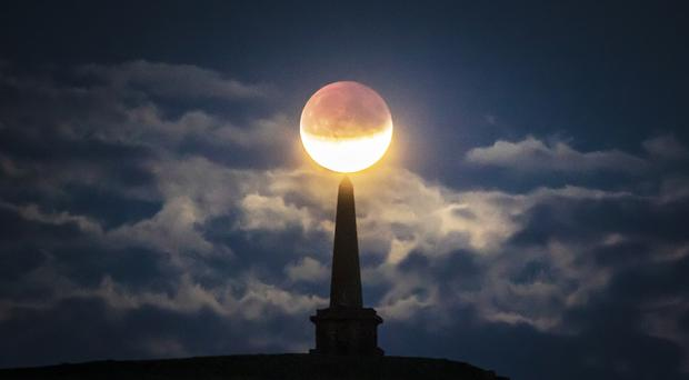 The partial lunar eclipse visible above Stoodley Pike near Todmorden in West Yorkshire (Danny Lawson/PA)