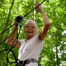 Eileen Noble, 84, navigates a treetop crossing as she becomes the oldest person to complete the Go Ape Treetop Challenge at Leeds Castle, Maidstone in Kent (PA)