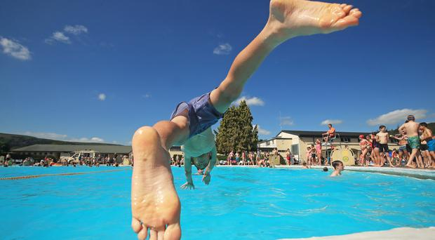 Freddie Ward jumps into the water at Ilkley outdoor pool and lido in West Yorkshire (Danny Lawson/PA)