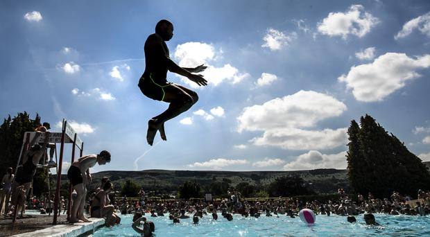 People enjoy the sun at an outdoor pool and lido in West Yorkshire as the UK is expected to edge towards its hottest ever July (Danny Lawson/PA)