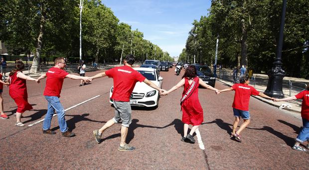 Greenpeace protesters blocked The Mall in London as Conservative party leader Boris Johnson heads to Buckingham Palace (Greenpeace/PA)