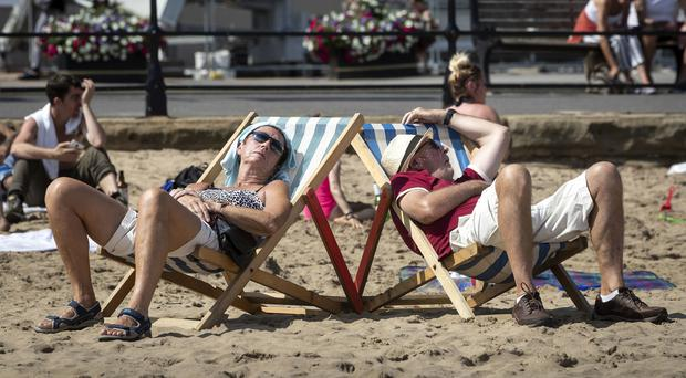 People sunbathe on Scarborough beach amid scorching conditions (Danny Lawson/PA)