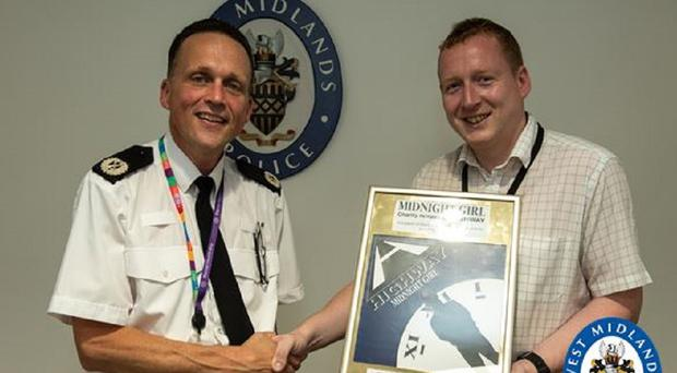 Pc Will Salt presenting ACC Chris Johnson with his single- Midnight Girl (West Midlands Police/PA)