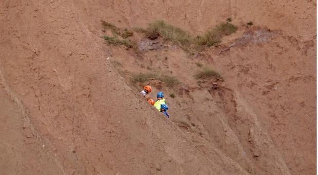 Coastguard crew rescuing a man and a woman from Filey Brigg in North Yorkshire (Owen Scrimshaw/PA/PA)