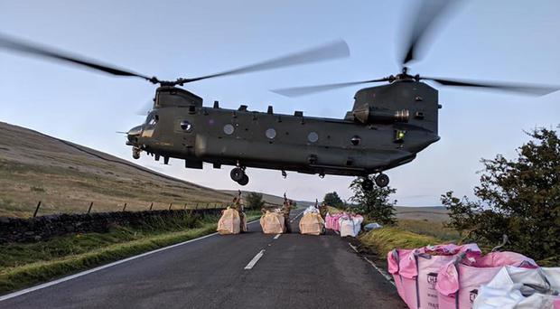 The RAF Chinook has been dropping sandbags on to the damaged area of the dam wall (RAF Benson/MoD/PA)