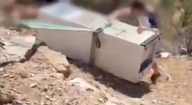 A man was filmed throwing a large fridge across a barrier and down into the hillside while laughing (@AUGC_Comunica/Twitter/PA)
