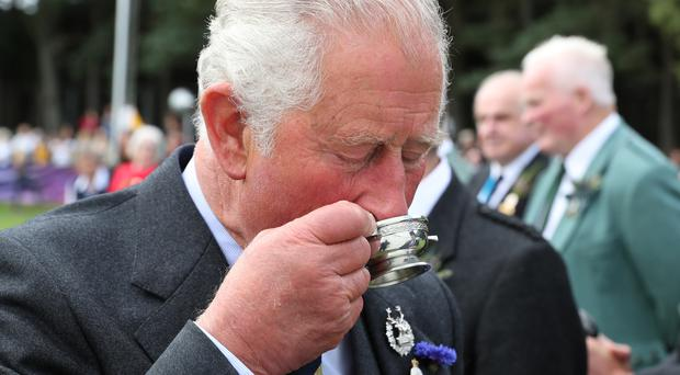 The Prince of Wales drinks a whisky given to him by Clan Farquharson president Alan Caig at the Ballater Highland Games (Andrew Milligan/PA)