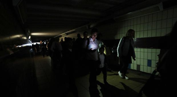 People walking in complete darkness at London's Clapham Junction station (Yui Mok/PA)