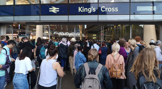People waiting outside of King's Cross station as a power cut hit services (Lewis Pennock/PA)