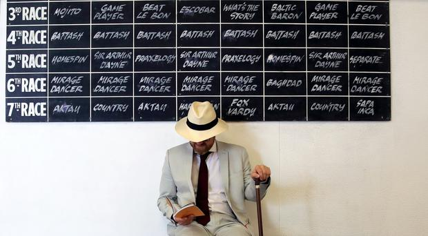 A racegoer studies his race card on day four of the Goodwood Festival (PA)