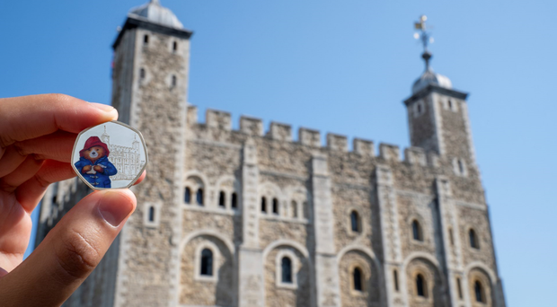 New Paddington Bear coins will enter circulation, including one showing Paddington at the Tower of London (Royal Mint/PA)