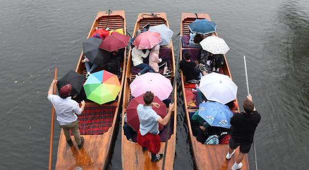 People shelter under umbrellas as they punt along the River Cam (PA)