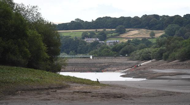 The water level continues to drop as work continues to shore up the dam at Toddbrook Reservoir near the village of Whaley Bridge (Joe Giddens/PA)