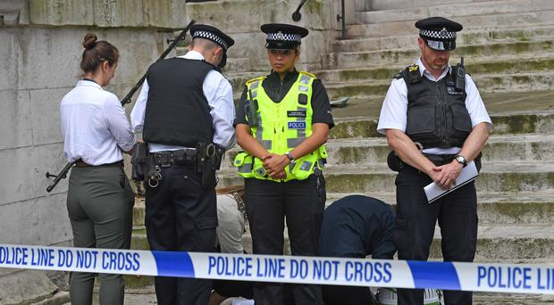 Investigators look at items ouside St John's Smith Square church in Westminster after an incident in which a man was stabbed outside the Home Office (PA)