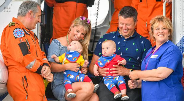 Jennie Powell, centre left, and Rich Powell, centre right, with their twin boys Jenson, left, and Ruben, right, who were celebrating their first birthday meeting HM Coastguard chief crewman Ian Copley, left, and midwife Jane Parke (Ben Birchall/PA)