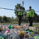 Officers pay their respects in front of tributes left near the scene in Sulhamstead, Berkshire, where Pc Andrew Harper died (Yui Mok/PA)