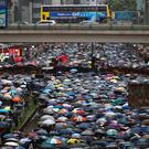Demonstrators carry umbrellas as they march along a street in Hong Kong (Vincent Yu/AP)
