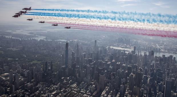The Red Arrows fly down the Hudson river in New York, with signature red, white and blue smoke trails (Sgt Ashley Keates/RAF/MoD)