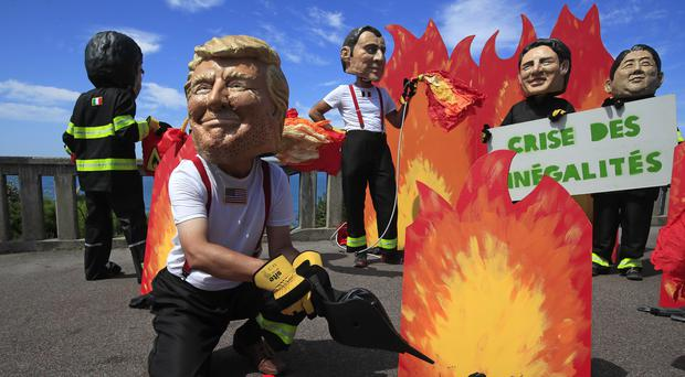 A man wearing a mask President Donald Trump is joined by other 'world leaders' during a protest ahead of the G-7 summit in Biarritz, France Friday, Aug. 23, 2019. The European Union and Germany are backing French President Emmanuel Macron's call to put the Amazon fires on the agenda of this weekend's G-7 summit of world leaders in France. Other leaders are from left: Italian Premier Giuseppe Conte, French President Emmanuel Macron, Canadian Prime Minister Justin Trudeau and Japanese Prime Minister Shinzo Abe. (AP Photo/Peter Dejong)