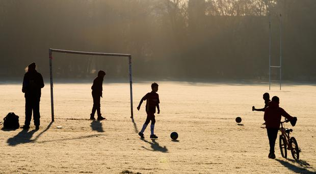Children playing football (John Walton/PA)