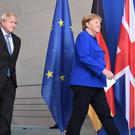 Prime Minister Boris Johnson walks with German Chancellor Angela Merkel in Berlin as he arrives ahead of talks to try to break the Brexit deadlock (PA)