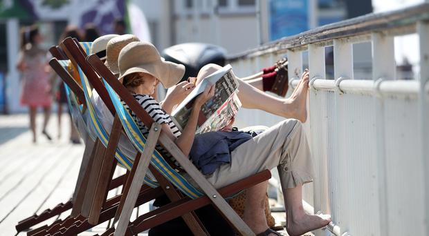 People in deckchairs enjoy the warm weather on Bournemouth pier in Dorset.