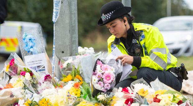 A police officer arranges flowers left near the scene where Thames Valley Police officer Pc Andrew Harper died (PA)