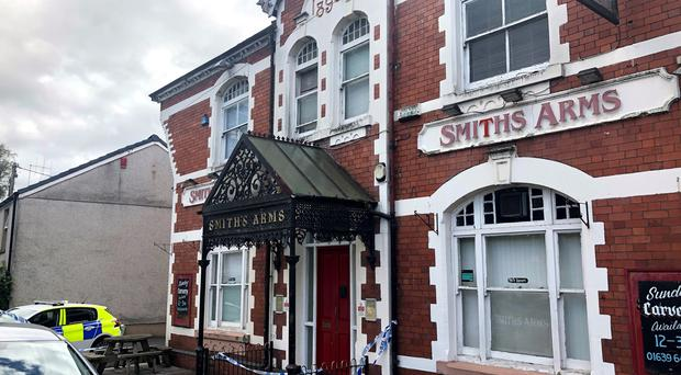 Police tape and vehicles outside the Smiths Arms pub in Neath, South Wales (PA)