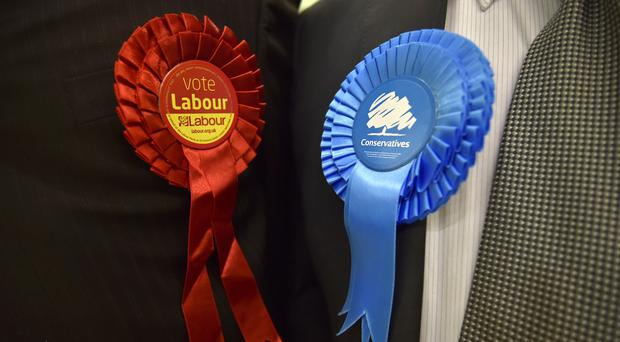 Conservative Party and Labour Party rosettes (Hannah McKay/PA)