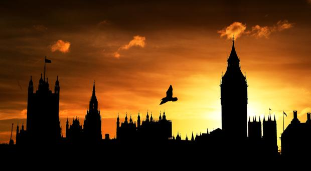The sun sets behind the Houses of Parliament in London (Andrew Matthews/PA)