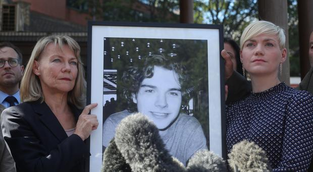 The mother and sister of Owen Carey hold his portrait outside court (Yui Mok/PA)