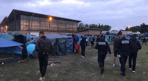 French police officers move migrants on from a camp in Dunkirk (Care4Calais/PA)
