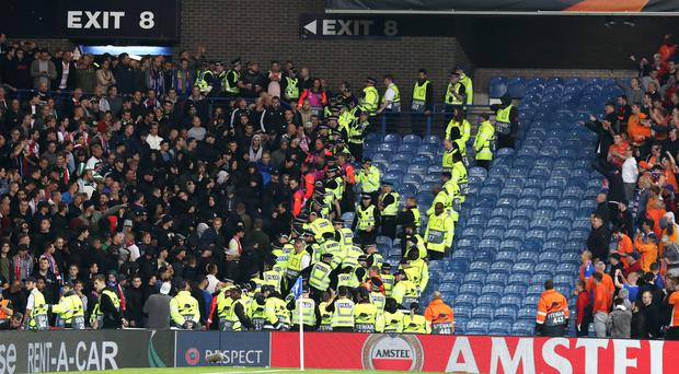 Fans clash with police in the stands (Andrew Milligan/PA)