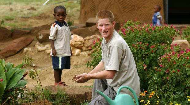 Prince Harry with young orphan Mutsu Potsane, 4, at the Mants'ase Children's Home in Lesotho (John Stillwell/PA)