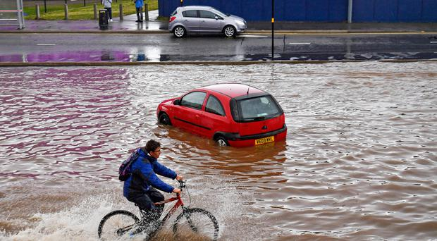 A man cycles past a stranded car on a flooded road in Birmingham city centre on Tuesday (Jacob King/PA)