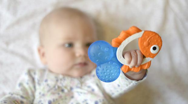 A baby holds a teething ring in the style of a fish (Andrew Matthews/PA)