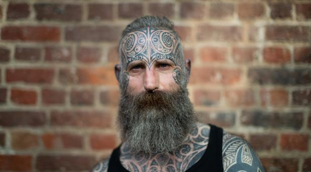 A man stands for a portrait during the International tattoo convention at Tobacco Dock in east London (Aaron Chown/PA)