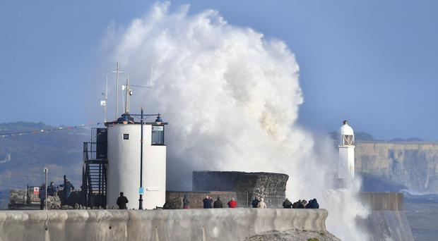 People gather to watch huge waves crash against the harbour wall at Porthcawl, Wales (Ben Birchall/PA)